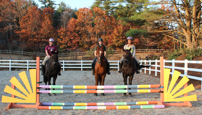 Three riders posing at a jump